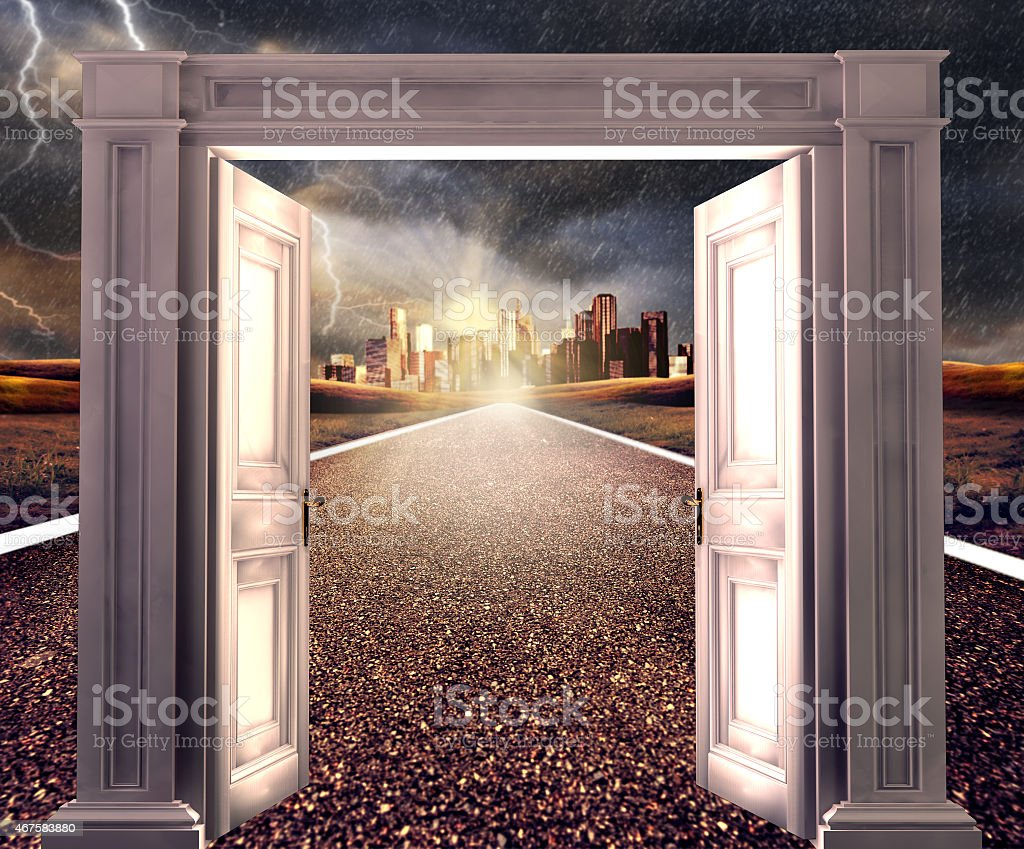 Large white open doors leading to an empty road and city stock photo