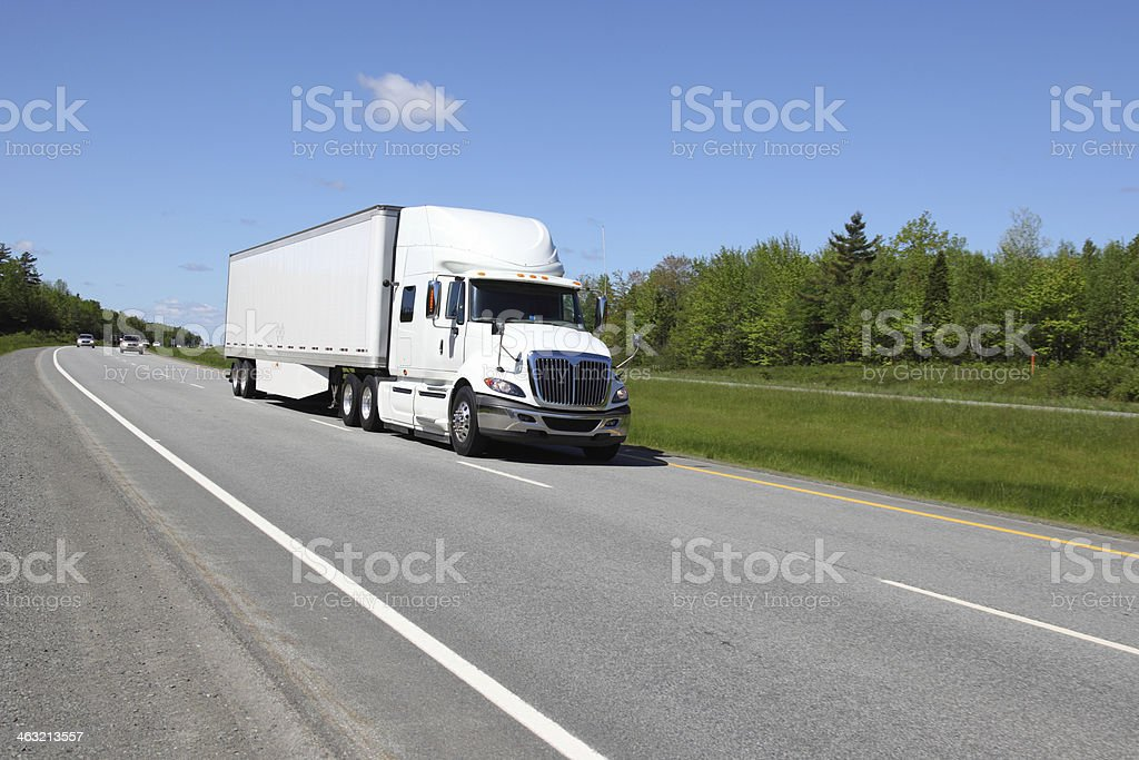 Large white semi-truck driving down an empty road stock photo