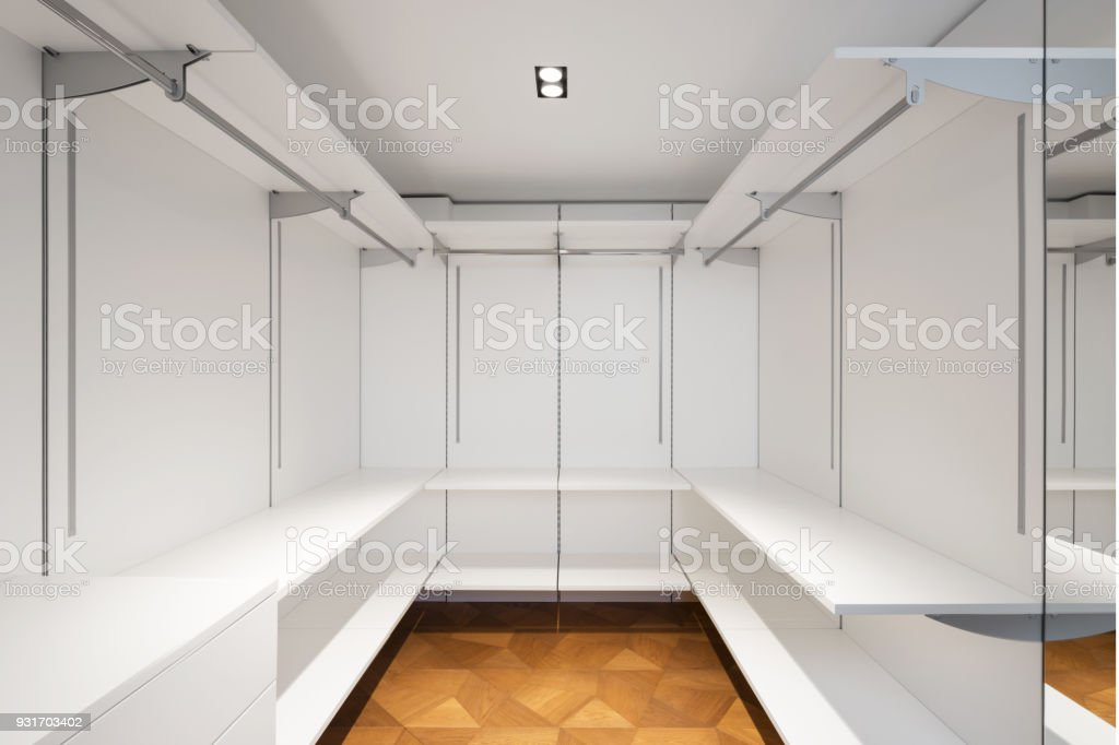 Large white walk-in closet with parquet stock photo