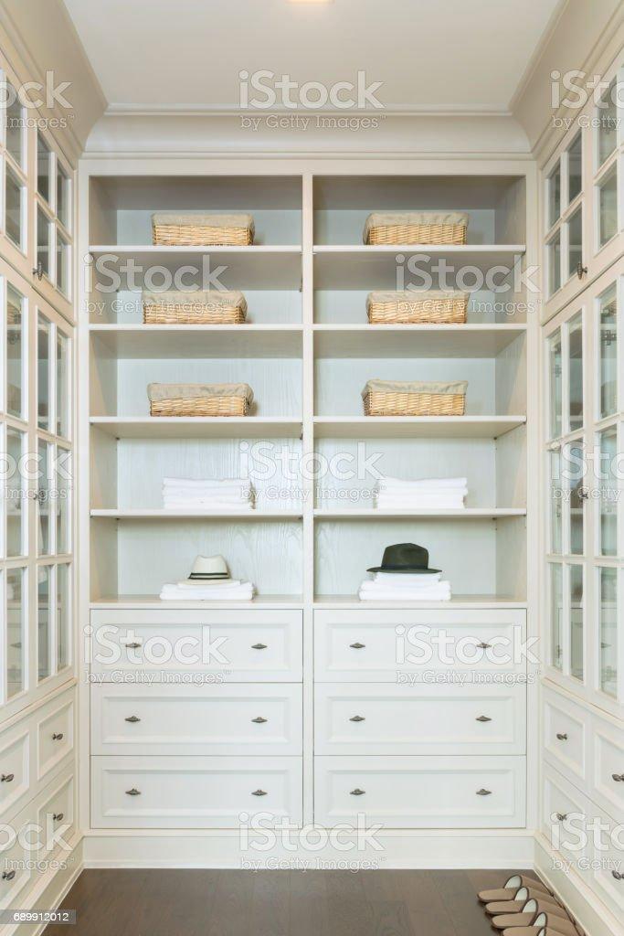 großen weißen begehbaren Kleiderschrank mit Regalen zu Hause – Foto