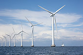 istock Large white windmills in the sea with a sailboat 157475904