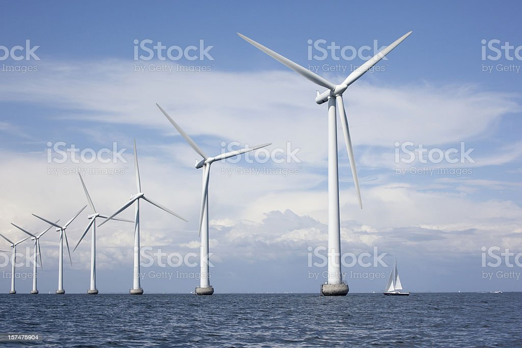 Large white windmills in the sea with a sailboat stock photo