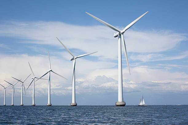 large white windmills in the sea with a sailboat - windmolen stockfoto's en -beelden