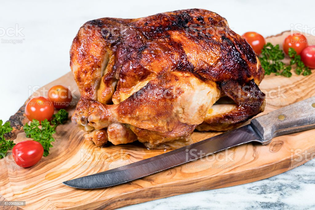 Large whole chicken ready to be carved on wooden server stock photo