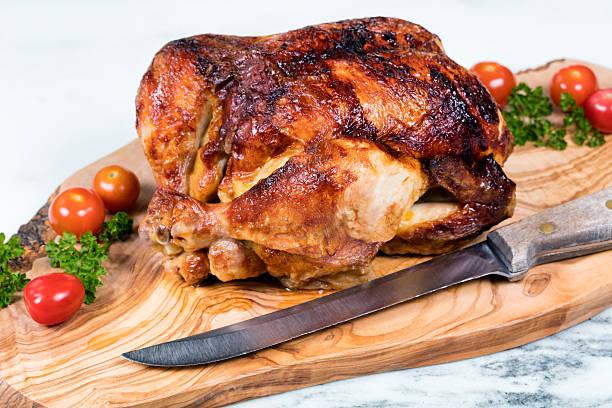 grande di pollo intere pronto per essere il server in legno intagliato - girarrosto foto e immagini stock