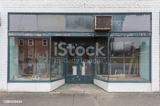 Large window storefront with green and white paint in small town business district