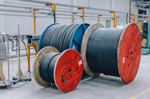 Large and red colour wooden cable spools stands in large electronic cable factory warehouse indoor