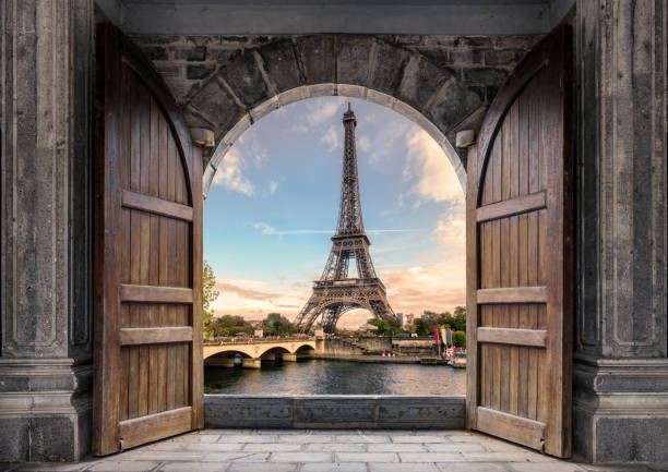 Large wooden door open with Eiffel Tower on Seine River on sunset at Paris stock photo