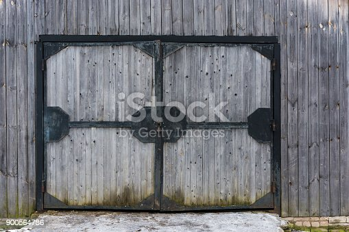 Large wooden gate in a black iron frame with an open lock in the middle.