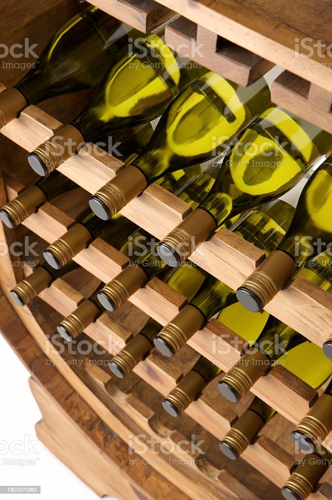 Large wooden rack filled with identical bottles of white wine royalty-free stock photo