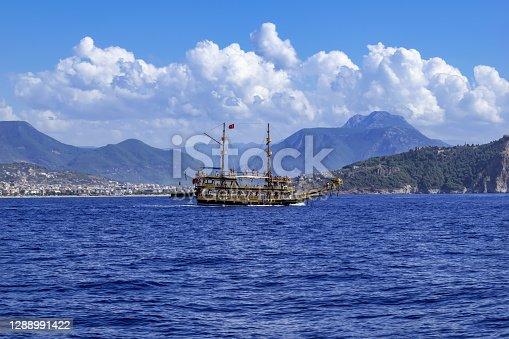 Large wooden vintage galleon on the background of Alanya (Turkey) among the mountains - view from the Mediterranean Sea. Pirate ship on the background of the city on the rocky coast. Beautiful panorama
