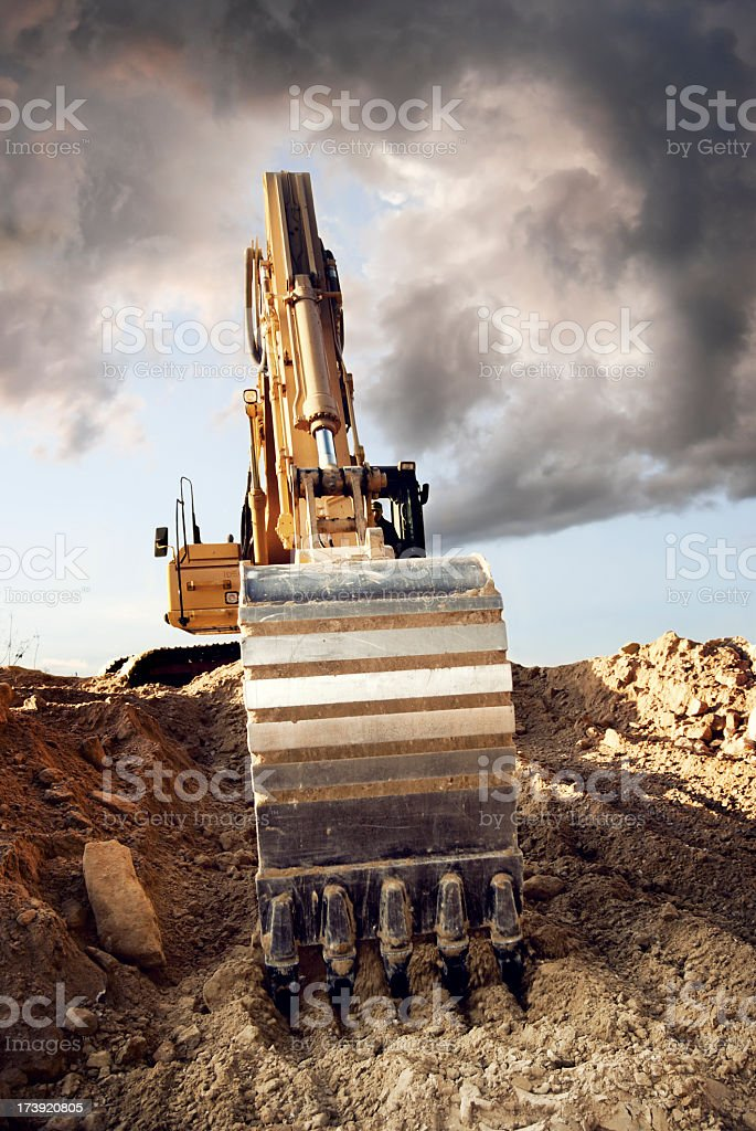 Large Yellow digger dragging its claw through the dirt royalty-free stock photo