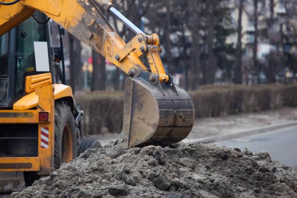 en stor gul grävmaskin står mitt i gatan - excavator bildbanksfoton och bilder