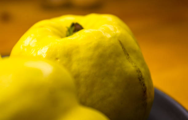 große gelbe quitte früchte auf einem keramik-platte, mit anis, zimt und walnüssen - quittenkuchen stock-fotos und bilder