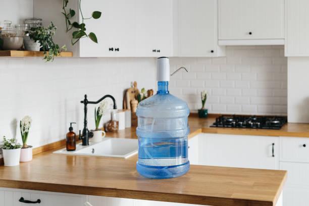 Eine größere Flasche sauberes Wasser 19 Liter mit automatischem weißen Pomp im Inneren der Wohnung mit einer weißen Küche im Hintergrund. – Foto