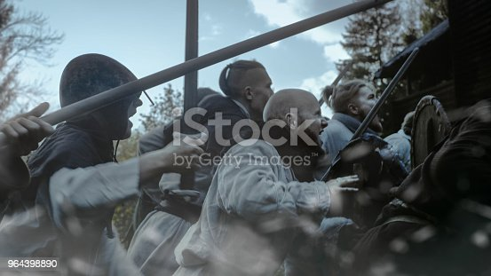 istock Large-Scale Medieval Battle Reenactment. Violent Tribe of Warriors Attack Wooden Fortress Wall, They Climb Ladders, Guards Try to Defend Fortification.They Fight with Axes, Swords, Spears, Bows, and Shields. 964398890