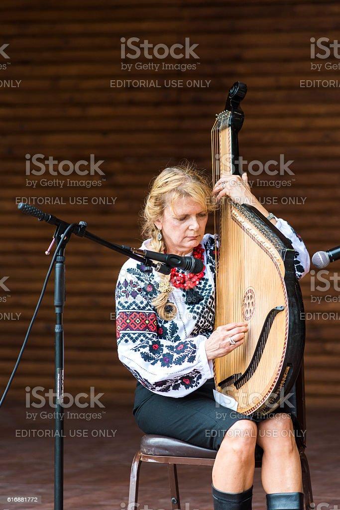 Larisa Pastuchiv-Martin playing bandura musical instrument стоковое фото