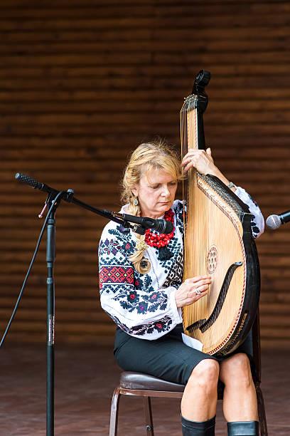Cтоковое фото Larisa Pastuchiv-Martin playing bandura musical instrument