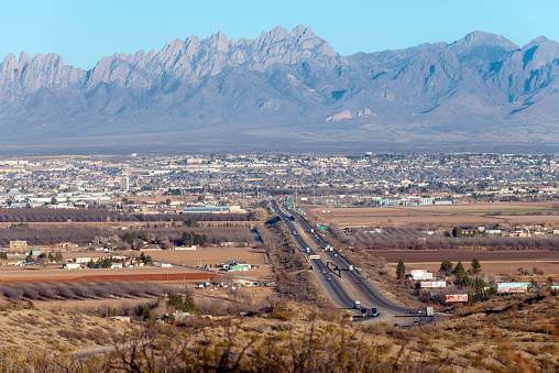 View from high vantage point, mountains in background, cityscape, bright sunny day, blue sky, interstate 10, city in distance, high angle view