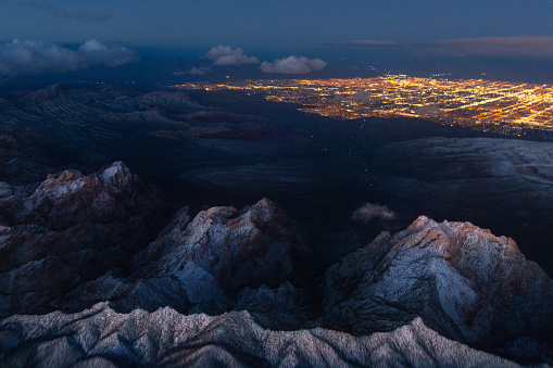 An Aerial of of The Spring Mountains and the lights of Las Vegas in the distance. This photo was taken in winter with fresh snow.