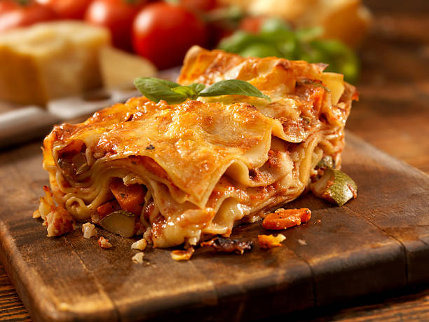 Lasagna Primavera Authentic Italian Vegetarian Lasagna on a Cutting Board with Ingredients -Photographed on Hasselblad H3D2-39mb Camera primavera stock pictures, royalty-free photos & images
