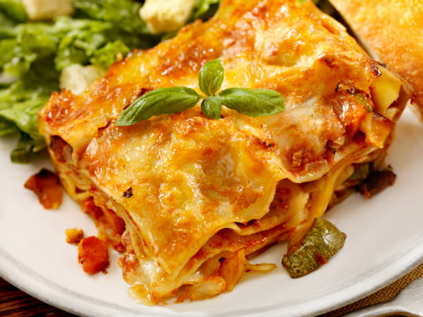 Lasagna Primavera Authentic Italian Vegetarian Lasagna with Ceaser Salad and Foccacia Bread -Photographed on Hasselblad H3D2-39mb Camera primavera stock pictures, royalty-free photos & images