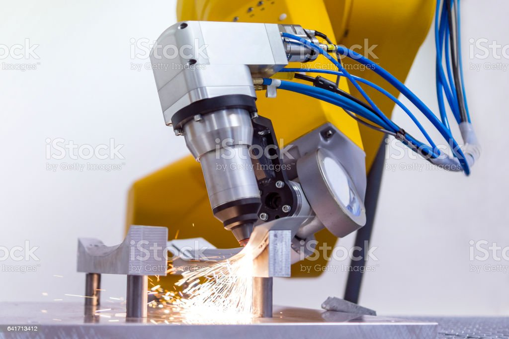 laser cutting of metal on robotic arm stock photo