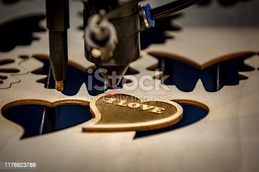 Close-up of laser engraving and cutting machine and just finished heart shaped wooden badge