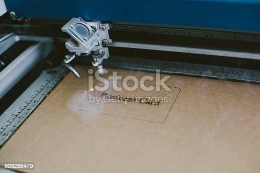 istock Laser engraving business card from recycled cardboard 603288470
