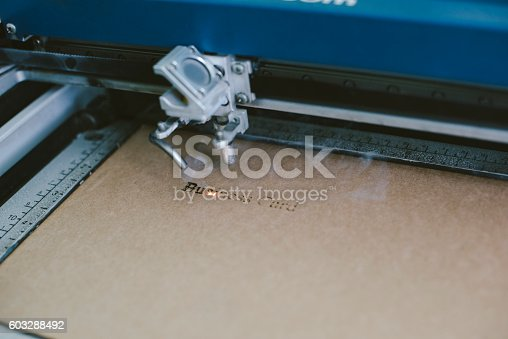 istock Laser engraving business card from recycled cardboard 603288492