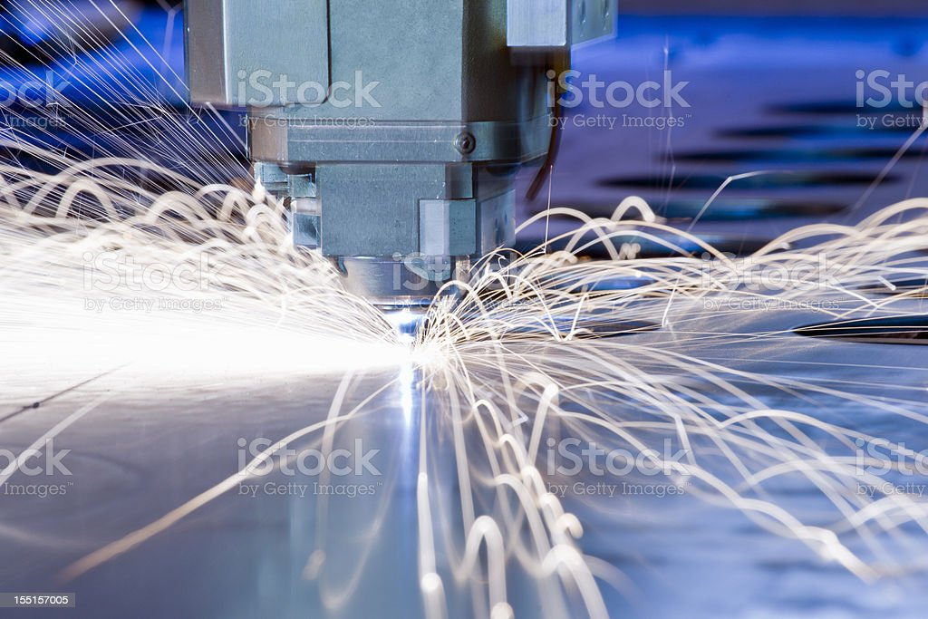 CNC laser metal-cutting tool in operation with sparks stock photo