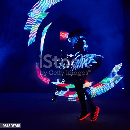 istock Laser show performance, dancers in led suits with LED lamp, very beautiful night club performance, party 961826756