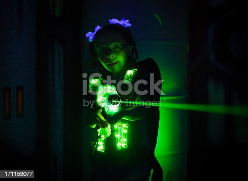 A little girl playing laser tag.  Photographed at a high ISO under black light to capture true look and feel of game.