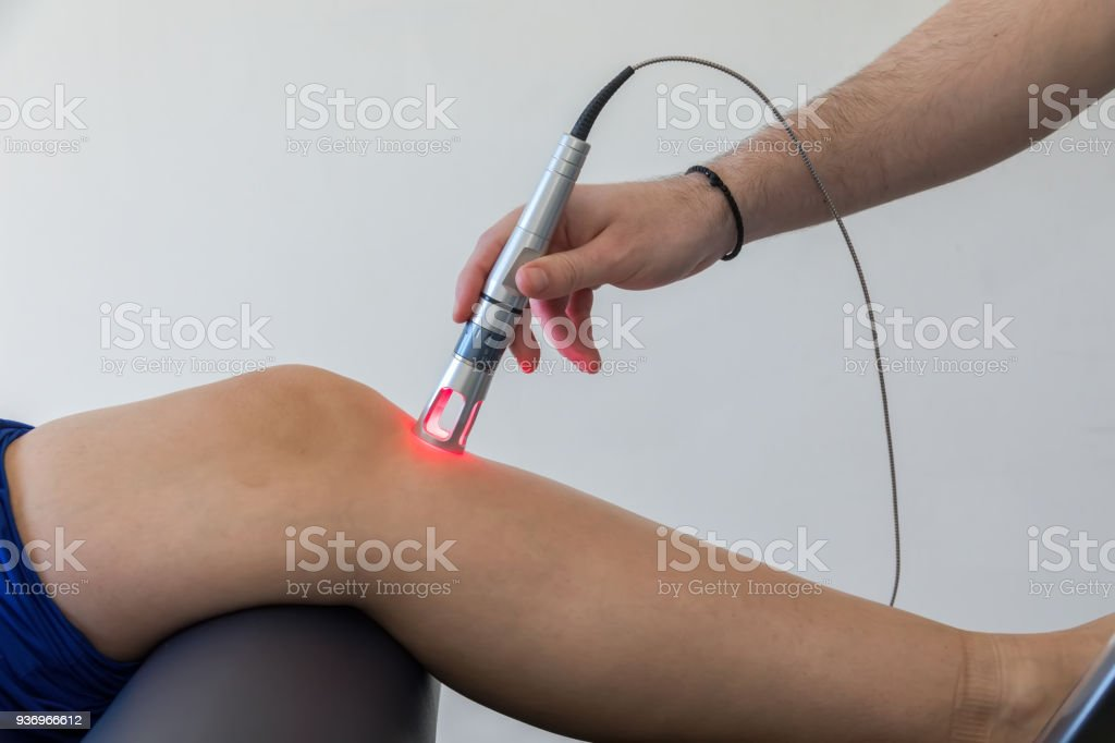Laser therapy on a knee used to treat pain stock photo