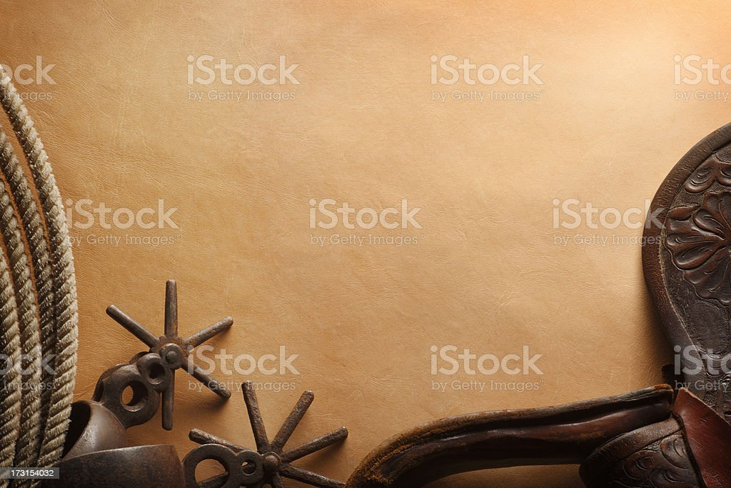 Lasso, spurs, and leather saddle flap on brown leather surface stock photo