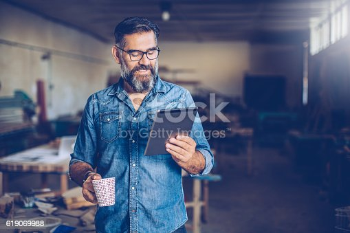 A carpenter cheking his project on touchpad just before starting to work. He's holding coffee in one, and tablet in other hand. Workshop in background, lot of tools and crafts of different type.