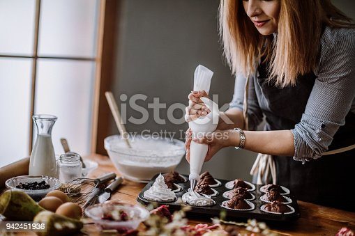 Woman Decorating Muffins Using Cream Syringe