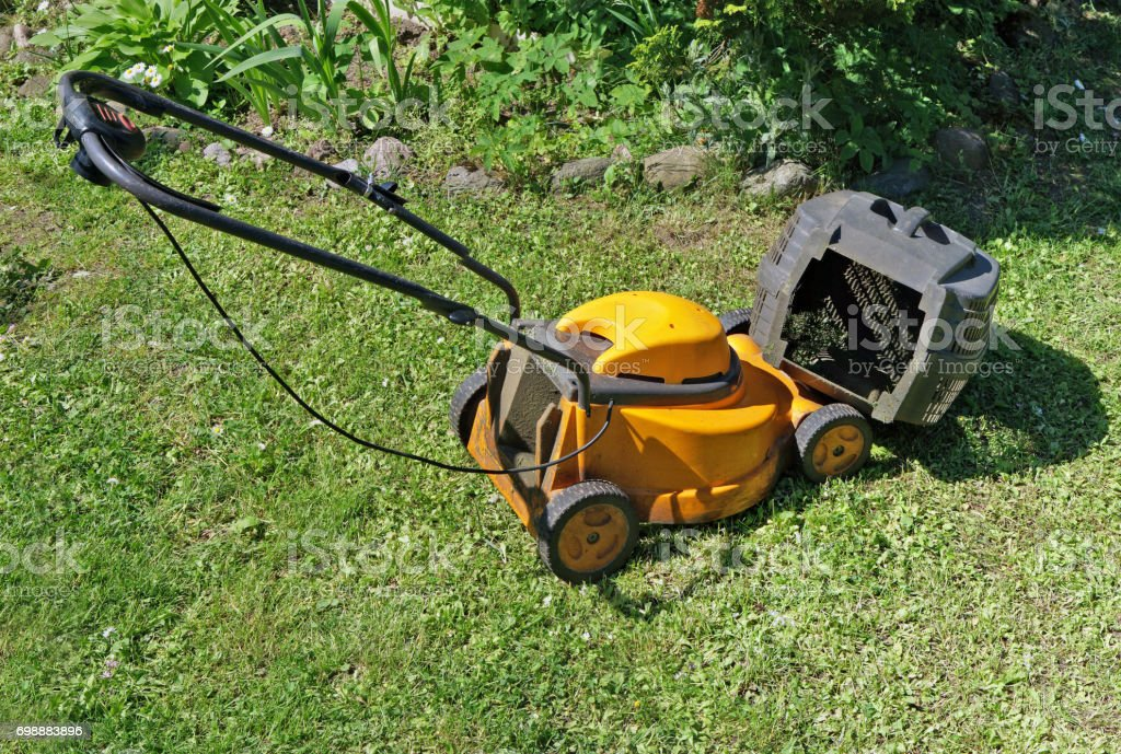Last day of life of an old electric lawn-mower. As the motor has burned down - tomorrow the device will be dumped stock photo