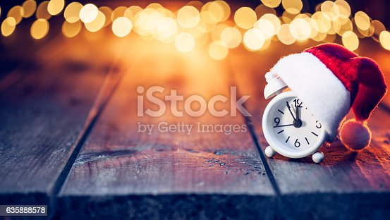 White retro alarm clock with santa hat on old planks. Defocused christmas lights in the background.
