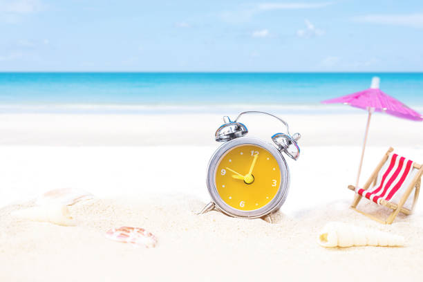 last minute to count down for travel metaphor by old retro clock on sand beach stock photo