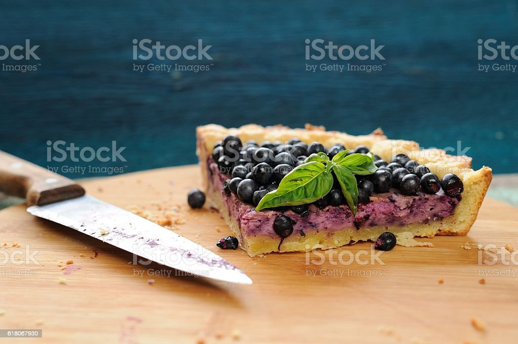 Last piece of blueberry pie decorated with basil leaves stock photo