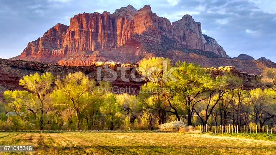 Last rays of sunset light against peaks in Zion as seen from Rockville Utah looking across grass pasture fields toward Mount Kinesava