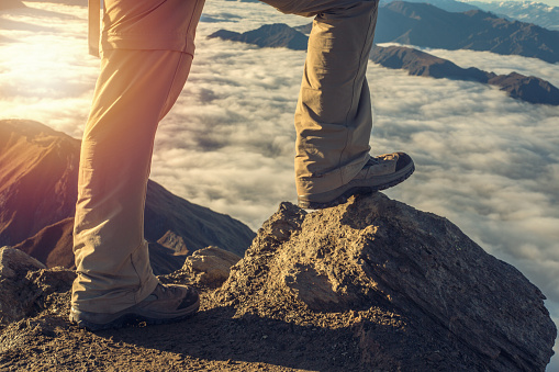Close up on hiker's boots standing on mountain peak above the clouds.