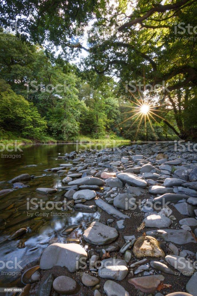 Laatste zonlicht op de rivier Lune met zonsondergang ster licht op rivieroever stenen rustig landschap foto