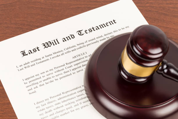 Last will and testament on yellowish paper with wooden judge gavel; document is mock-up Last will and testament on yellowish paper with wooden judge gavel; document is mock-up last stock pictures, royalty-free photos & images