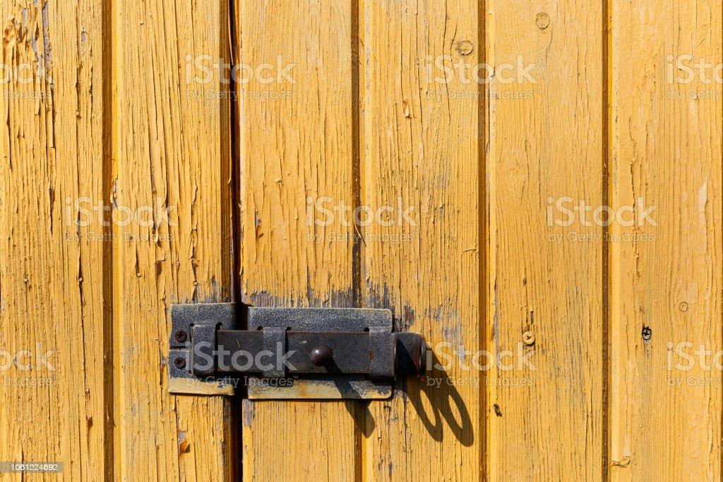 Trava na parede de madeira amarela. Velhas gasto pranchas de madeira com rachado cor pintam. Plano de fundo. Madeira de textura. - foto de acervo