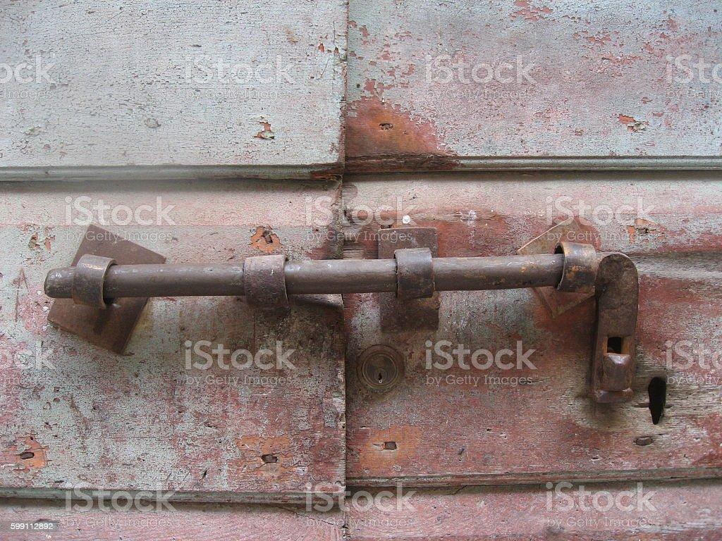 Latch rusty door bolt on weathered wood stock photo