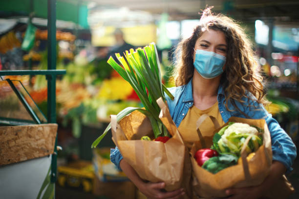 Late 20's woman going grocery shopping after business reopened during coronavirus pandemic stock photo