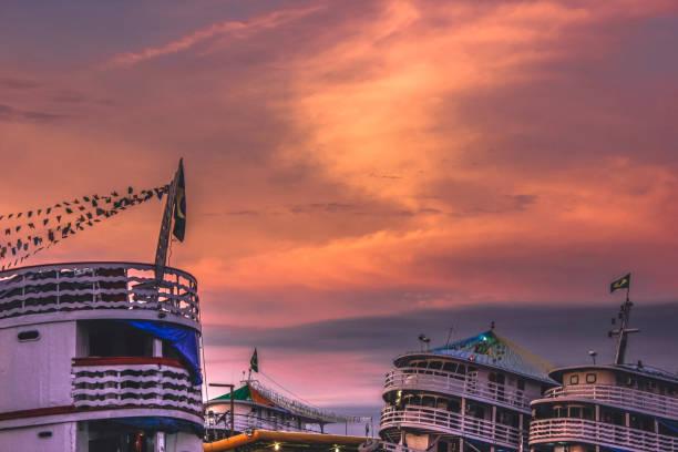 Late afternoon and boats Registro de um fim de tarde no porto da cidade de Manaus. Na composição aparece em primeiro planos os pisos elevados dos barcos de passageiros que cruzam a região amazônica, ao fundo um céu de nuvens com tons intensamente arroxeados. manaus stock pictures, royalty-free photos & images