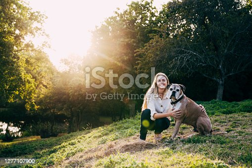 Sunny view with lens flare of fawn colored Boxer sitting on hillside next to smiling Caucasian woman in early 20s and looking at camera.